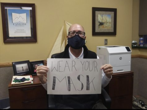 Picture of Principle Leavitt holding sign reminding student to wear their masks.